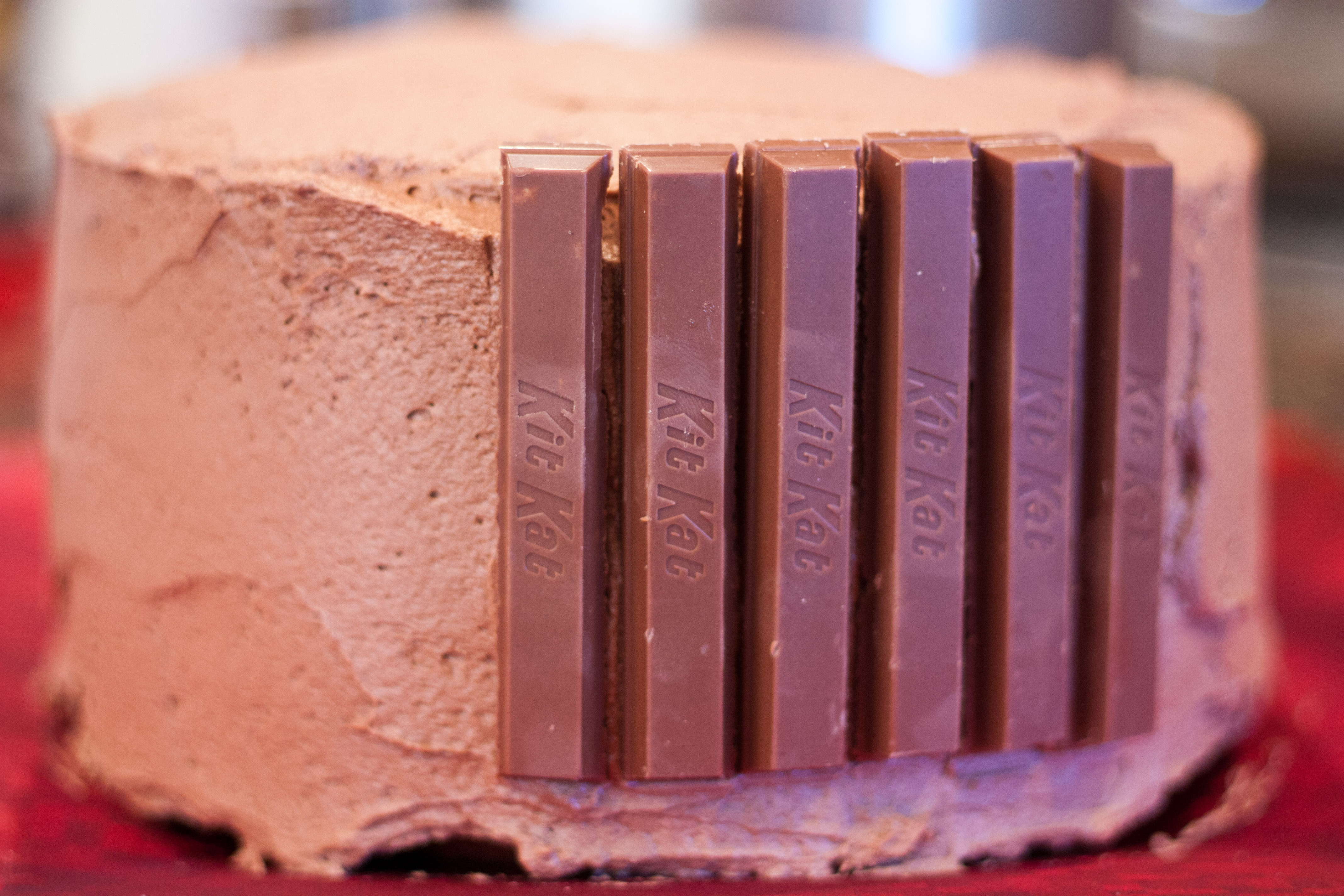Working quickly, place kit kat bars side by side all around the edge ...