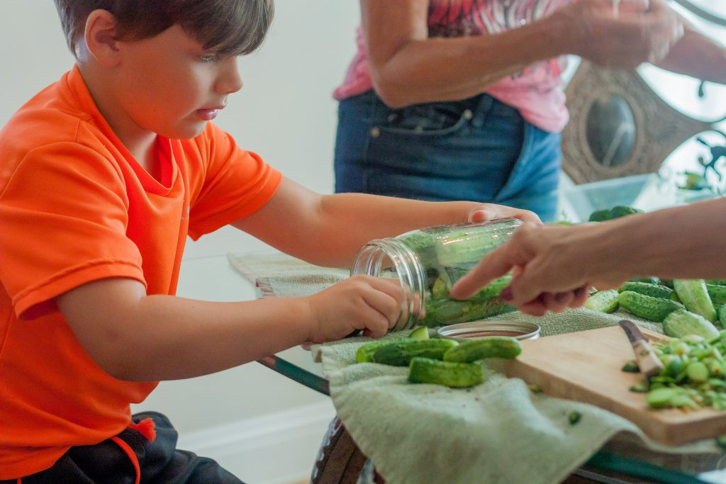 Joel helping us pack cucumbers into jars | JenniferCooks.com