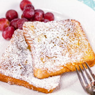 easy french toast dusted with powdered sugar on a plate with a side of grapes